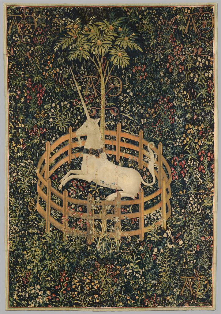 Photograph of a 14th-century tapestry depicting a unicorn lying on a field of complex floral designs. The unicorn is contained by a small fence that it could easily jump over, but it chooses to chill with the pomegranate tree instead. The unicorn wears a very fancy lapis and gold collar.